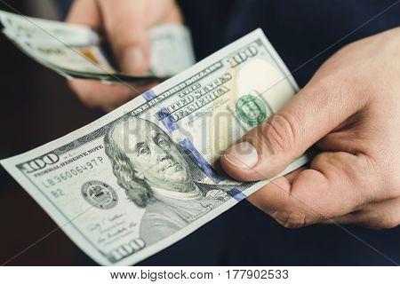 Male hand gives one hundred dollars banknote close-up view business and finance concept