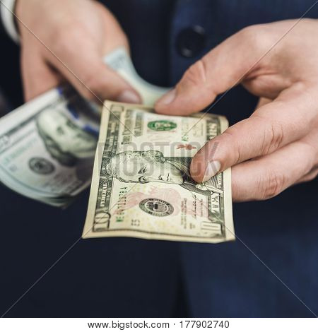 Male hand gives one ten dollars banknote close-up view business and finance concept