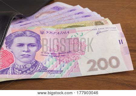 Wallet with ukrainian money currency hryvnia on wooden background