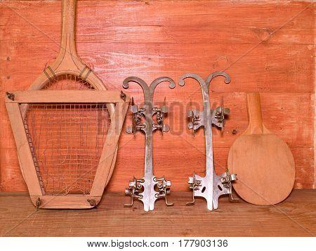 Vintage Ice Skates, Tennis Racket And Table Tennis Racket On Wooden Background. Retro Ice Skates Ten