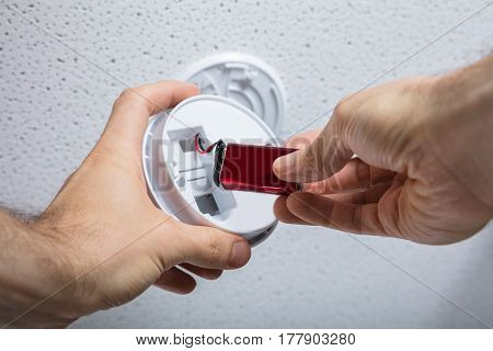 Close-up Of A Person Hand Removing Battery From Smoke Detector On Ceiling Wall