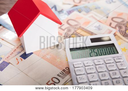 Close-up Of A House Model On Euro Bank Note Near Calculator
