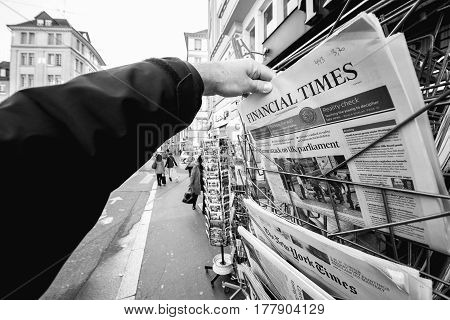 PARIS FRANCE - MAR 23 2017: Black and white image of man purchasing Financial Times newspaper from press kiosk newsstand featuring headlines following the terrorist incident in London at the Westminster Bridge