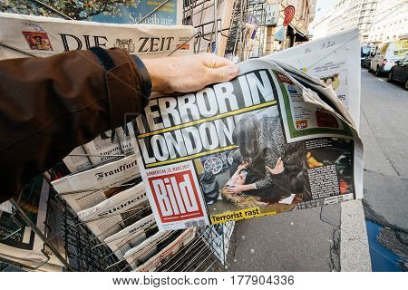 PARIS FRANCE - MAR 23 2017: Man purchases a newspaper German Bild from press kiosk newsstand featuring Terror in London headlines following the terrorist incident in London at the Westminster Bridge