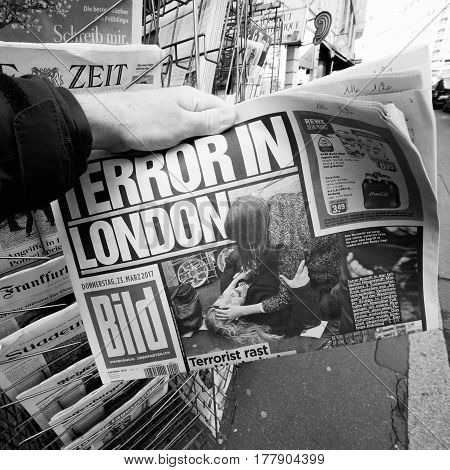 PARIS FRANCE - MAR 23 2017: Black and white Man purchases newspaper German Bild from press kiosk newsstand featuring Terror in London headlines following the terrorist incident in London at the Westminster Bridge