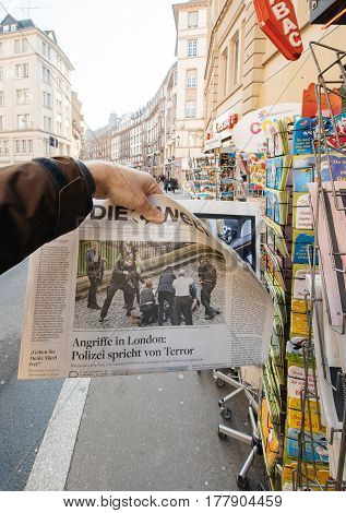 PARIS FRANCE - MAR 23 2017: Man purchases Die Welt newspaper from press kiosk newsstand featuring headlines and images with Police following the terrorist incident in London at the Westminster Bridge