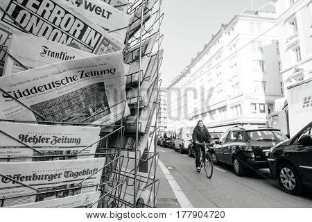 PARIS FRANCE - MAR 23 2017: Senior cyclist woman passing near Suddeutsche Zeitung and other international magazines covers at press kiosk newsstand featuring headlines following the terrorist incident in London at the Westminster Bridge