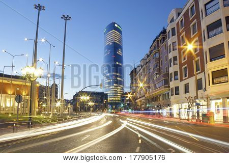 BILBAO SPAIN - MARCH 24 2017: The Iberdrola tower at sunset. It's the highest building on the Basque country Spain. Photo taken from Elcano street with the light trails of the traffic.
