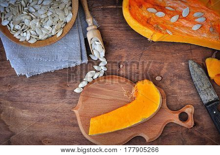Piece of fresh pumpkin and pumpkin seeds on a brown table top view