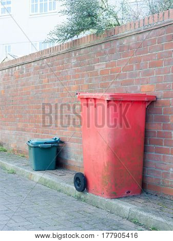 A red and green bin resting against a wall.