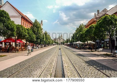 KOSICE SLOVAKIA - JUNE 12 2014: Kosice Main Street (hlavna) with pedestrians and bicylces passing by. The national theatre (Divadlo) can be seen in the background)