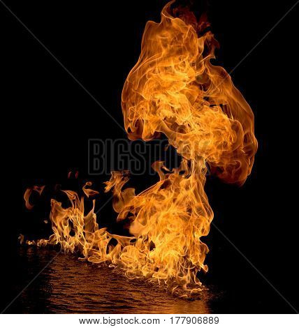 Gasoline fuelled flames on a body of water at night