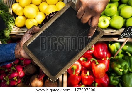 Hand pointing at blackboard in aerial view on vegetable and fruit