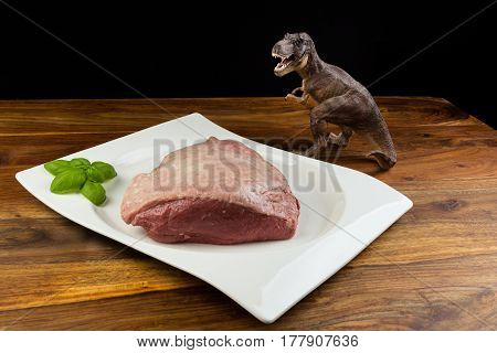Dinosaur Tyrannosaurus Rex Staring A Full Piece Of Raw Cow Beef (picanha), With Basil On A White Dis