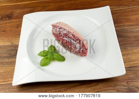 Slice Of Salted Raw Cow Beef (picanha) And Basil Leaves On A White Dish And Vintage Natural Wood Tab