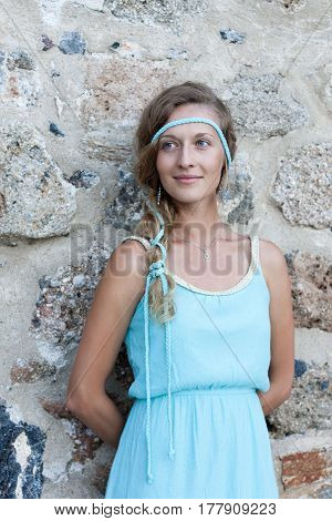 Young Woman Standing With Medieval Stone Walls Behind