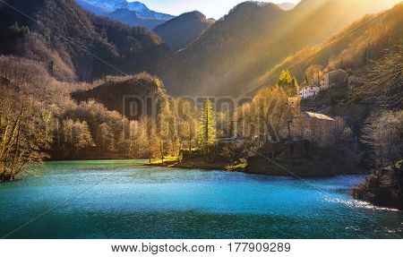 Isola Santa medieval village church lake and Alpi Apuane mountains. Last sunbeam of the day. Garfagnana Tuscany Italy Europe