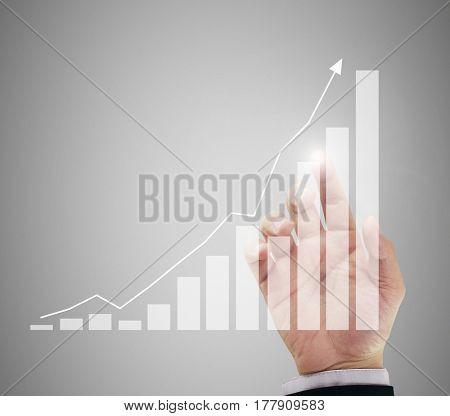businessman's hand behind trend graph