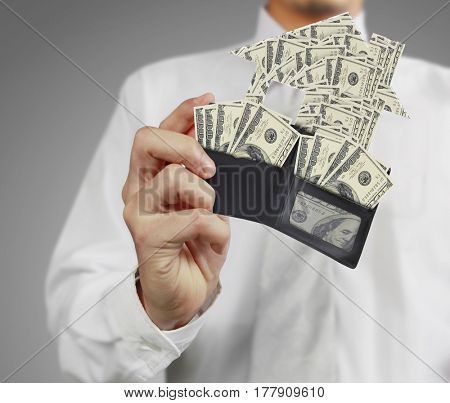 hand holds house made of money coming out of open wallet