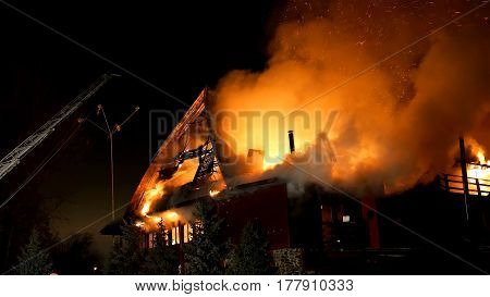 House building on fire at night. Blaze Inferno conflagration and combustion.
