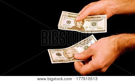 Man is counting money cash dollars bills in hands. Twenty and ten dollar banknotes closeup.