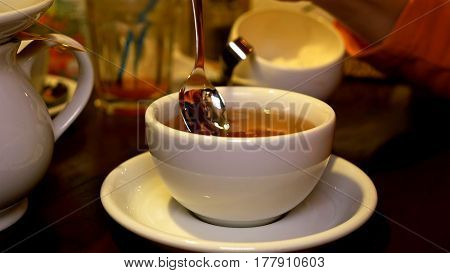 Pouring black tea into cup from teapot and stir. Tea time lunch snack breakfast dinner and supper relax concept.