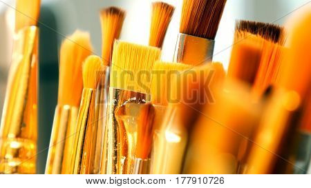 Artist paintbrushes. Set of different artist paint brushes in old crock close-up. Art studio concept. Selective focus footage with shallow DOF.