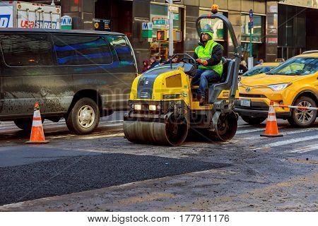 NEW YORK CITY - March 16 2017: road under construction asphalting in progress spring snow