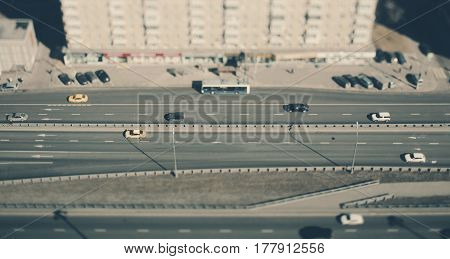 True tilt shift shooting of highway in metropolis from high above: residential building road in focus with cars and public transport crosstown traffic long shadows from street lanterns sunny day