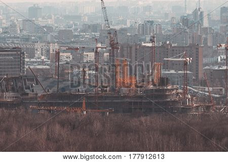 Close-up shooting from top of morning metropolitan city: huge unfinished stadium under construction with cranes scaffolding and beams residential buildings on hazy distance in background