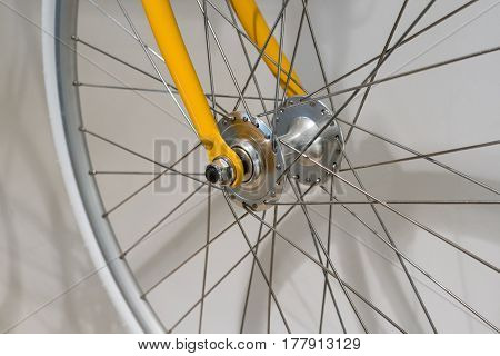 Closed Up of Front Bicycle Wheel on White Wall