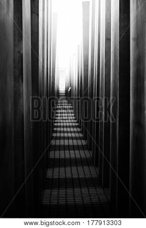 BERLIN, GERMANY - MAY 10: A narrow passage between the dark and threatening gray concrete blocks of the Memorial to the Murdered Jews of Europe leads to the light on May 10 2016 in Berlin.