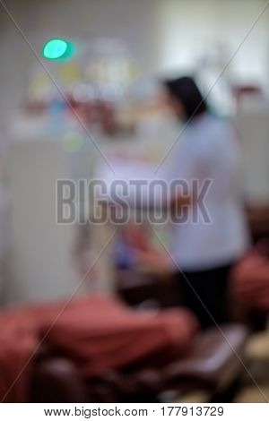 Writing on clipboard with patient in background in hospitalblurred photo