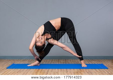 Young asian woman practicing yoga pose at yoga healthy sport gym yoga and meditation have good benefits for health. Photo concept for Yoga Sport and Healthy lifestyle