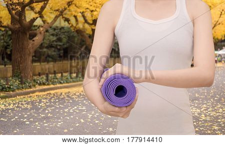 Young asian woman holding her yoga mat at outdoor park. Yoga and meditation have good benefits for health. Photo concept for Yoga Sport and Healthy lifestyle