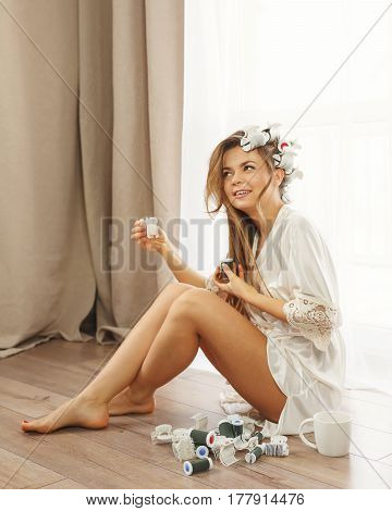 Lovely Young housewife sitting on the floor near the window. Girl in a bathrobe and curlers hair done. Good morning.