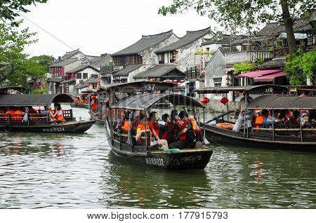 August 8 2015. Xitang Water Town China. Crowded tourist boats on the water canals of Xitang Town in Zhejiang Province China on an overcast day.