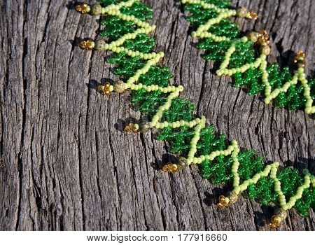 green bead-work lace on a wooden background. Soft selective focus and shallow depth of field