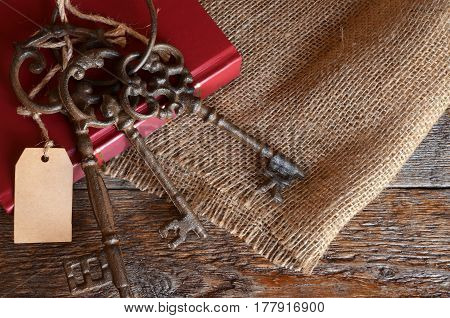 A top view image of antique cast iron keys and a red book on a wooden bench.
