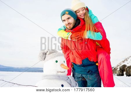 A happy couple is having a good time fooling around on a winter lake