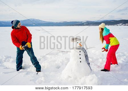 A happy couple is playing snowballs on a winter lake