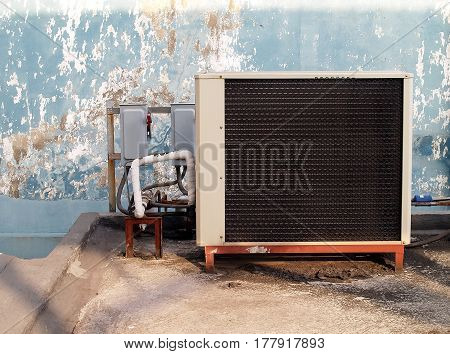 air conditioning compressor on outside terrace and two circuit breaker boxes with old blue wall background
