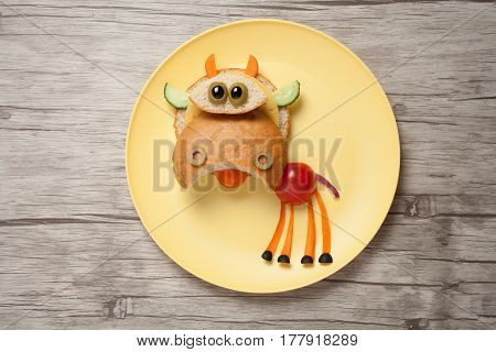 Cow made of bread and fresh vegetables on plate and table