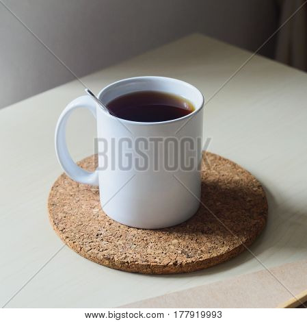 White cup of black tea and cork coaster on wooden table