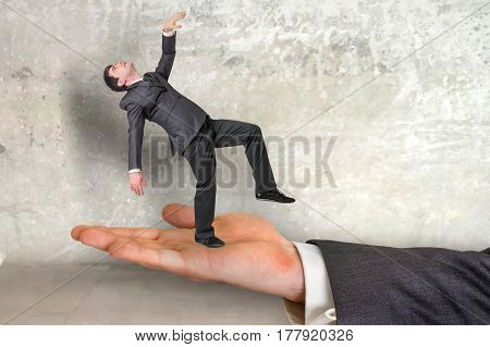 Small Businessman Dancing On The Palm Of His Boss