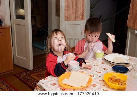 children eating lunch at home healthy food concept kids enjoying bread and yogurt sibling emotional faces healthy breakfast for brother and sister