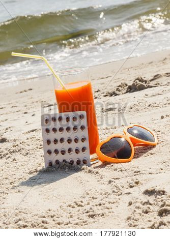 Medical Pills, Carrot Juice And Sunglasses On Sand At Beach, Vitamin A And Beautiful, Lasting Tan
