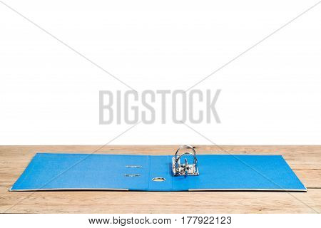 An open clerical folder for storing documents a blue with clip, lying on a wooden table on a white background