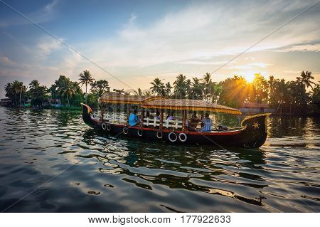 Boat Carrying Tourists Floating Down The River On A Background Of Palm Trees And Beautiful Sunset.