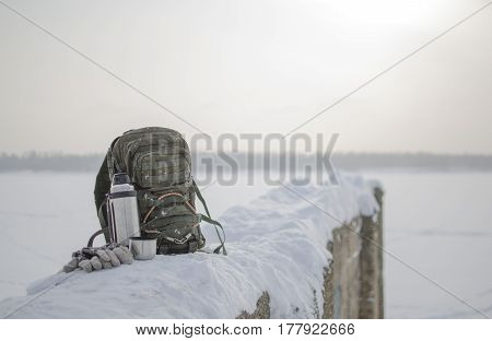 Рюкзак на волнорезе. На фотографии представлен туристический рюкзак и термос с чаем на волнорезе зимой.